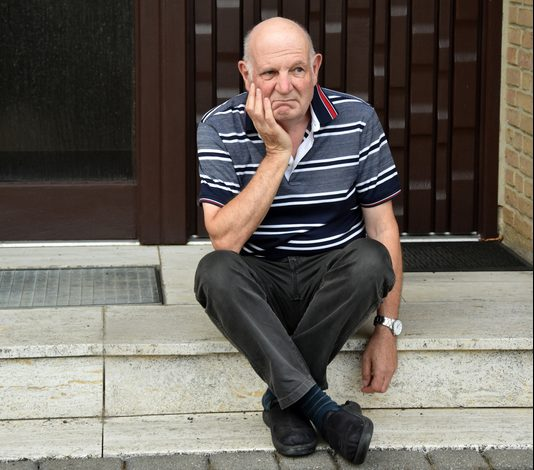 senior man locked out of his home, sitting on curb, upset.